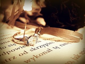 A sepia photo of a diamond ring on a book.