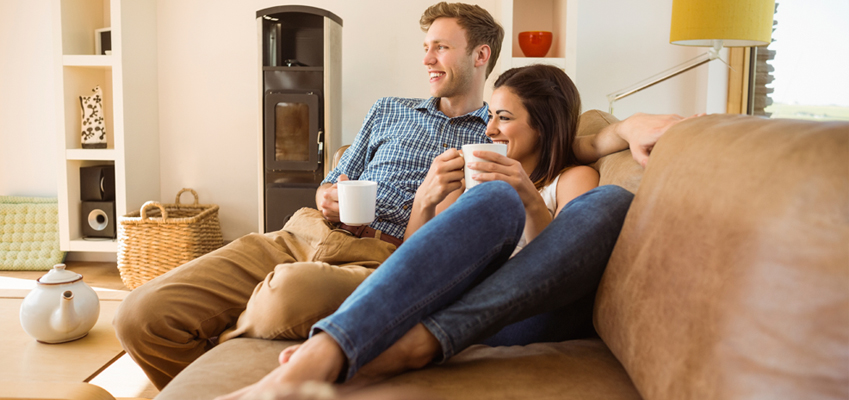Couple Sitting at Home Drinking Coffee