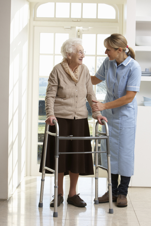 Woman Helping Elderly Person in Facility