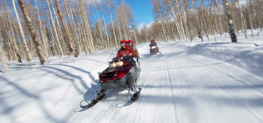 Friends Riding Snowmobiles Safely
